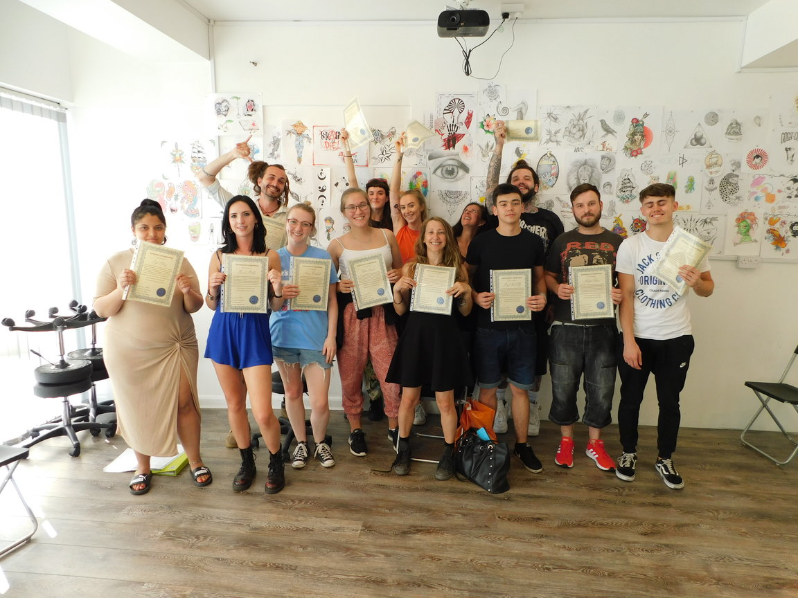 tattoo course ireland students holding pass certificates